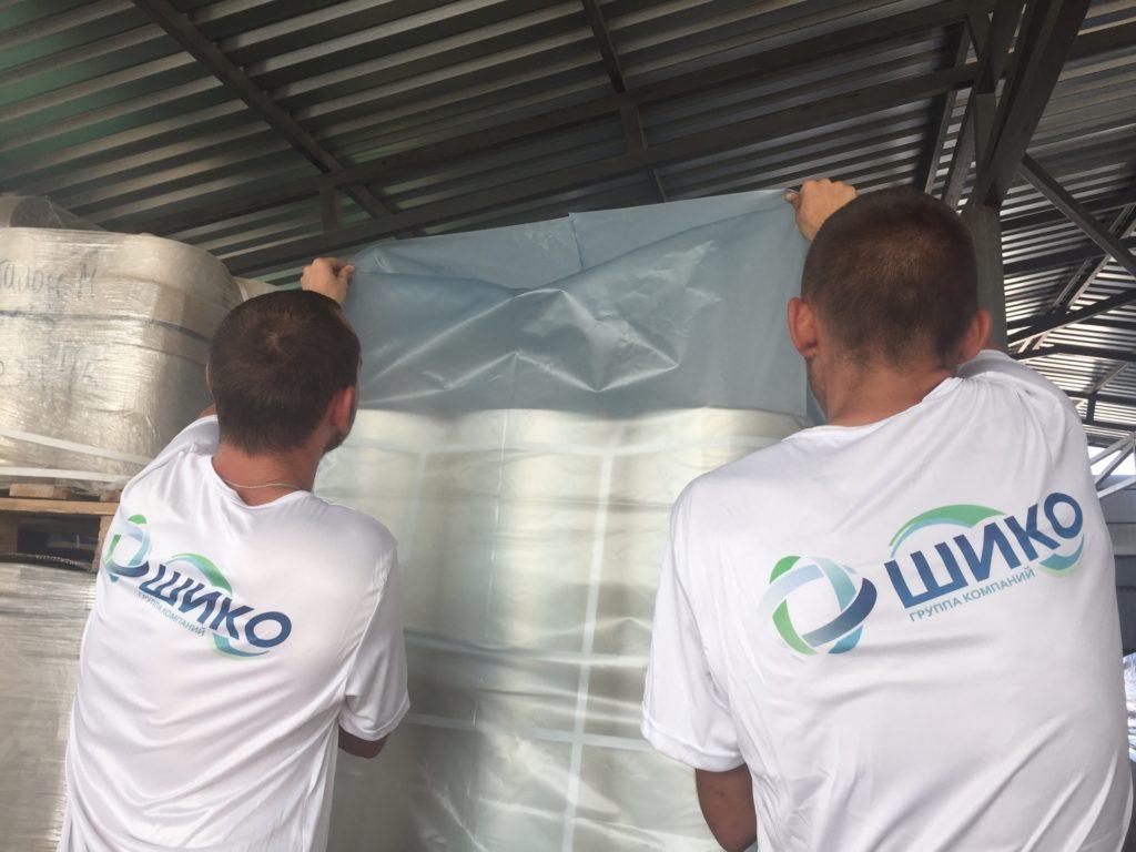 Работники компании ШИКО упаковывают продукцию в термоусадочный мешок